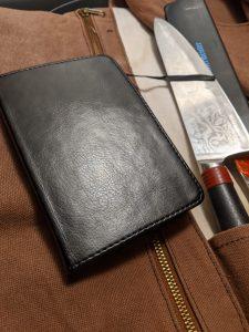 My black journal resting on knife roll